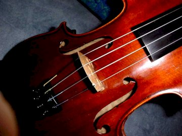 A beautiful violin - This beautiful violin that gives me a lot of pleasure. A violin sitting on top of a guitar.
