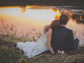 Narzeczeni siedzą nad stawem - Siedząca kobieta opiera się na ramieniu mężczyzny twarzą do jeziora podczas złotej godziny. Wa