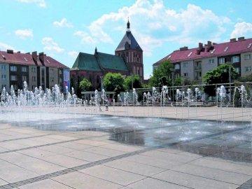 Koszalin Center - La photo montre le centre de Koszalin. Un grand bâtiment en brique.