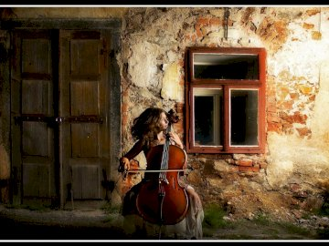 cellist - ---------------------------------------------. A person standing in front of a brick building.