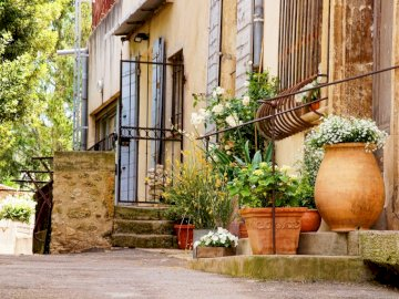 Prowansja - urocze małe miasteczko  ----------------. Wazon z kwiatami na budynku z cegły.