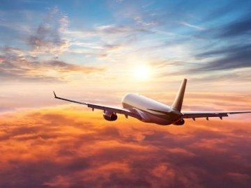 Voo de avião - Máquinas voando no céu. Um grande avião de passagem voando através de um céu nublado.