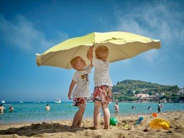 Praca zespołowa - Dwoje dzieci bawiące się pod parasolem na brzegu morza. Drøbak, Norwegia. Grupa ludzi na plaży z