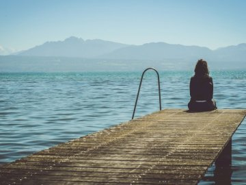 Admiring the lake from a pier - A woman sits on the end of a dock during daytime staring across a lake. A person sitting on a dock n