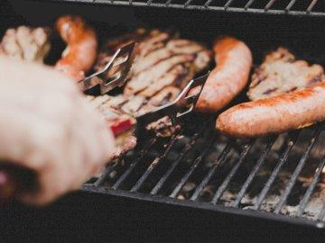 Czas na grilla - Osoba grillująca kiełbasę i mięso. Hamilton
