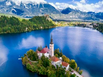 Island on the lake. - Landscape puzzle: island on the lake. A small boat in a body of water with Lake Bled in the backgrou