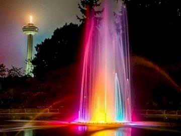 Podświetlana fontanna. - Podświetlana na kolorowo fontanna. Rozświetlone miasto nocą.