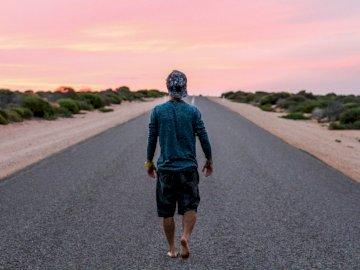 Samotny mężczyzna na asfaltowej drodze - Mężczyzna odprowadzenie na popielatej betonowej drodze. Kalifornia. Mężczyzna idący polną drog