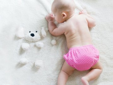 Dziewczynka - Dziecko na łóżku. Los Angeles, CA. Ręka trzymająca dziecko.