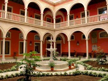 Sevilla so bunt und schön - Sevilla so bunt und schön. Ein großes Steingebäude mit vielen Fenstern.