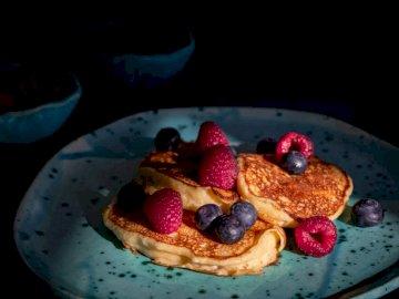 Naleśniki Ricotta, smaczne - Naleśnik z jagodami na talerzu. Bukareszt. Talerz jedzenia z plasterkiem ciasta na stole.