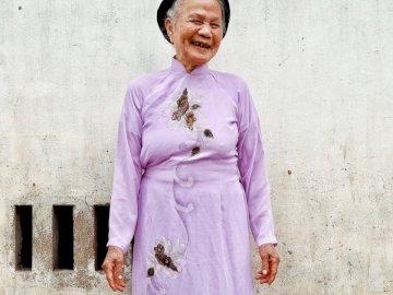 La vieillesse ne la fait pas perdre - Femme, debout, porter, chapeau Viet Nam. Une personne portant une robe rose debout devant un immeubl