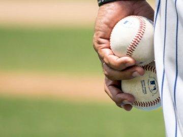 Valencia, Venezuela - Persona in possesso di due palle da baseball. Venezuela. Una persona in possesso di una mazza da bas