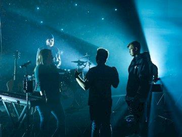 Rétro-éclairé, les gens - Groupe de membres du groupe discutant sur scène. Un groupe de personnes debout sur une scène.