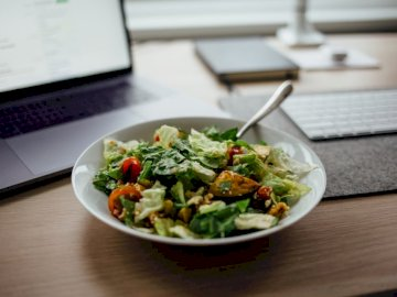 Healthy Paleo Salad - Salad on white ceramic bowl on top of table near laptop. Belgium. A bowl of food sitting on a table.