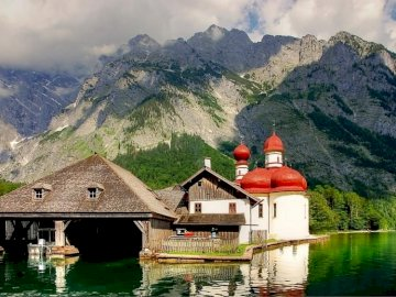 At the mountain lake. - Orthodox church with a red roof above a mountain lake. A house with a mountain in the middle of a la