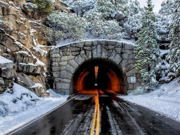 Túnel de carretera. - Entrada al túnel del camino debajo de la montaña. Un tren cubierto de nieve.
