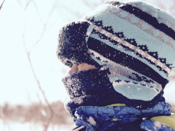 Person in Mützen und Schal an - Person, die schwarzen und blaugrünen gestreiften Hut zur Schneezeit trägt. Ontario, Kanada. Ein St
