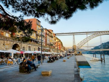 Porto  ------------------ - ----------------------------------------------------. Grupa ludzi przechodzących przez most nad akw