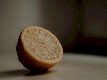 Drücken Sie etwas Saft - Geschnittene Zitrone auf weißem Tisch. Frankreich.