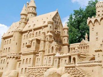 Castillo de arena - Rompecabezas: un gran castillo de arena. Una estatua frente a un edificio.