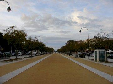zu Fuß in San Lucar de Barrameda - zu Fuß in San Lucar de Barrameda. Eine Person, die einen Drachen am Straßenrand fliegt.