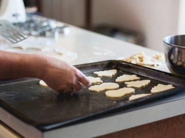 Ma mère et moi avons un - Personne tapissant des biscuits de forme variée sur une plaque à pâtisserie à l'intérie