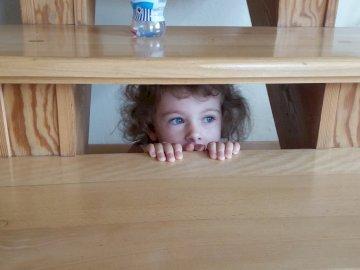 dobra kryjówka pod schodami - dobra kryjówka pod schodami. Mała dziewczynka siedzi na drewnianej podłodze.