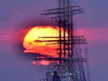 łódź żaglowa - żaglówka w zachodzie słońca. Duży statek w akwenie.