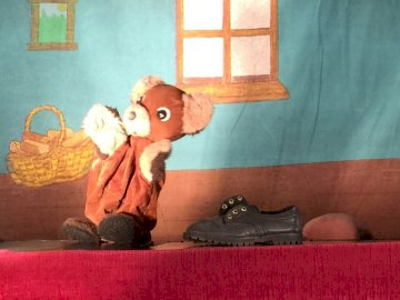 Mitchka the little bear - The little bear adored by small children. A large brown teddy bear sitting on top of a bed.
