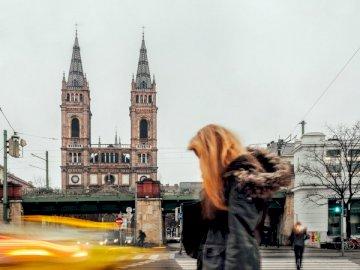 Zwei Frauen, zwei Kirchtürme, - . Eine Person, die eine Stadtstraße entlang geht.