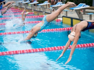 Swimmers are jumping from the - . A person swimming in a pool of water.