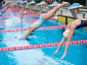 Pływacy skaczą z - . Osoba pływająca w basenie z wodą.