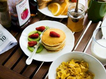 Pankejki na śniadanie - . Drewniany stół zwieńczony talerzami z jedzeniem na talerzu.