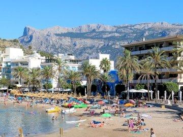 Maiorca Port de Soller - . Una spiaggia affollata di palme e un edificio sullo sfondo.