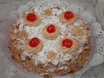 Almond cake with cherries - . A piece of cake sitting on top of a table.