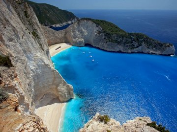 Greek island of Zakynthos - . A rocky cliff with water and a mountain in the background.