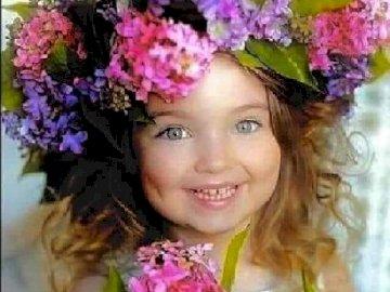 Chica. - Niño. Una chica encantadora. Una niña con una flor rosa.