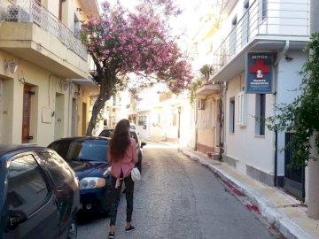urocza grecka uliczka - urocza grecka uliczka. Samochód zaparkowany z boku ulicy.