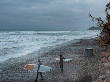 Surfer un jour brumeux. - Homme en chemise à manches longues noire tenant une planche de surf blanche marchant sur le bord de