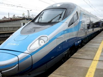 pendolino - the fastest train on Polish tracks. A blue and white passenger train stopped at a station.
