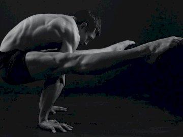 Naprawdę potrzebujemy darowizny. - Topless mężczyzna w czarnych szortach zginający ciało na wodzie. Kijów.