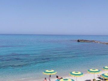Tropea strand - Tropea vackra strand. En grupp gräsmatta stolar som sitter överst av en sandstrand.