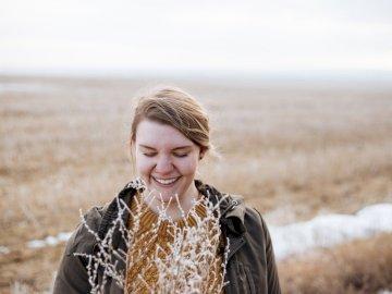 Sourire des yeux fermés dans le champ - Femme souriante près de fleur pendant faytime. Le Lower Mainland, Colombie-Britannique. Une personn