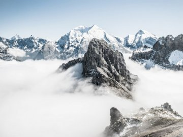 Mountain peaks above the clouds - Landscape photo of mountain alps. A snow covered mountain.