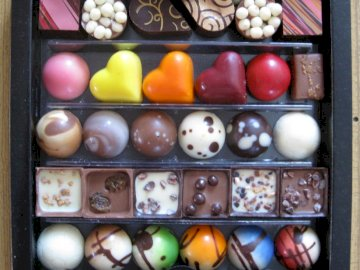 CHOCOLATES - Colorful chocolates in a box. A box filled with different types of fruit.