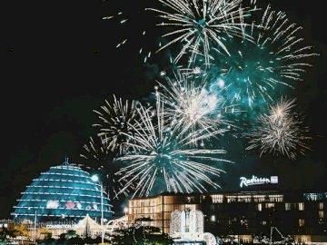 Obchody Nowego Roku Fajerwerki - Fajerwerki wyświetlają się nad budynkami miasta w nocy. Fajerwerki na niebie z zegarem Cosmo 21 w