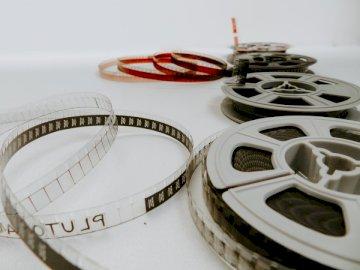 Rollos de película de 8 mm - Cuatro películas de carrete sobre mesa blanca. Groninga. Un plato blanco.