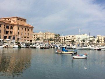 cittadina - Una piccola città sul Mar Mediterraneo. Una piccola barca in un porto accanto a uno specchio d&
