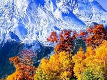 Autumn in the mountains. - Fairy land. Autumn landscape in the mountains. A view of a snow covered mountain.